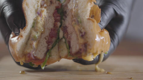 Close-up hands of the chef in black rubber gloves pressing halves of burger and Footage