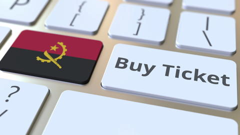 BUY TICKET text and flag of Angola on the buttons on the computer keyboard Photo