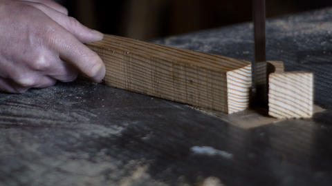 close up carpenter cuts a piece of wood with the use of a band saw Footage