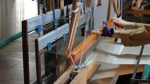 Traditional silk fabric loom. Old silk fabric weaving machine. Woman weaving silk fabric on loom Live Action