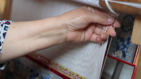 Carpet weaving close up. Senior woman's hand weaves traditional manual silk carpet loom Live Action