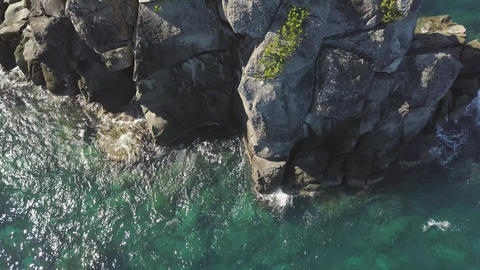 Sea waves splashing to rocky cliff drone view. Transparent sea waves breaking on Footage
