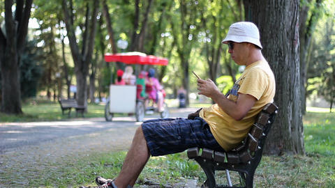 Man in hat and sunglasses is using smartphone in park on the bench. Man using smartphone while Live Action