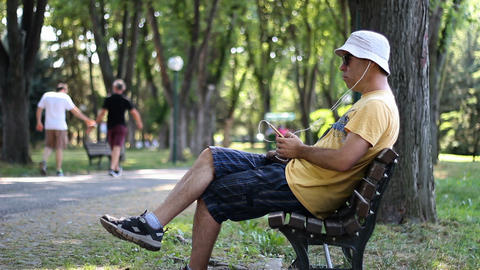 Man in hat and sunglasses listens to music sitting down on bench in park. Man listens to music with Live Action