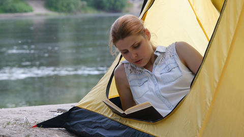Hiker girl reads book in camping tent. People living healthy active lifestyle Footage