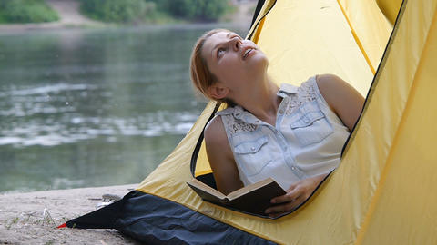 Young hiker girl reads book in camping tent, dreams and... Stock Video Footage