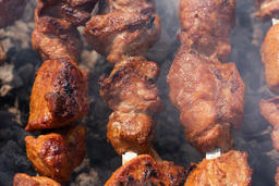 Close-up grilled pork shish kebab cooking on skewers charcoal grill Photo