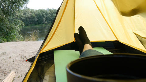 Hiker man sitting in a camping tent drinking tea or coffee. Solo tourist man Footage