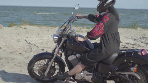 The girl wearing black helmet sitting on the motorcycle looking away on the Live Action