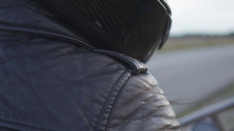 Unrecognized motorcycle rider in black leather jacket and helmet sitting on a Live Action