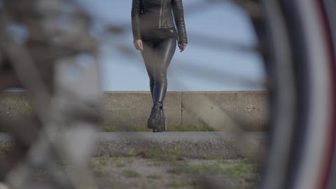 Adorable young caucasian female biker in black shoes and leather jacket comes to Footage
