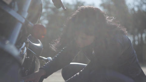 Caucasian girl fixing her motorcycle or checking condition in soft light close Footage