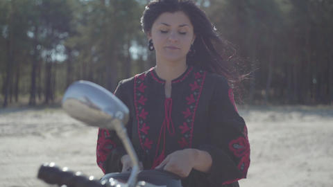 Caucasian girl sits on her motorcycle and wears a helmet. Skill woman in a black Live Action