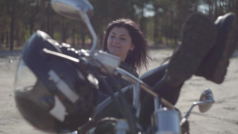 Pretty young caucasian woman in a black leather jacket and pants lying on a Footage