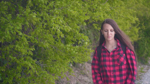 A young attractive girl in a red checkered shirt. The girl goes on the road Footage