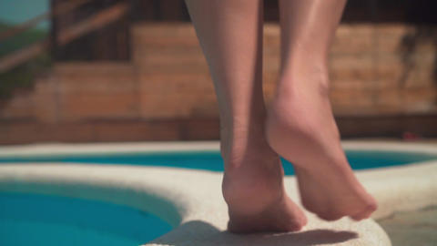 Close-up on a woman's legs as she tiptoes along the edge of the pool Footage