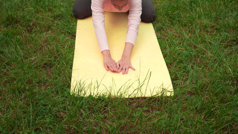 Pregnant woman doing yoga in the park on the carpet, doing in the pose of a Live Action