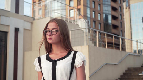 Caucasian business woman in white shirt and glasses walking down the street near Footage