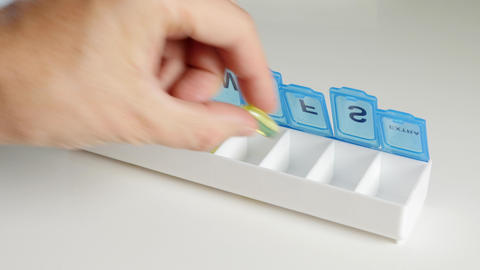 Adding Vitamins to a pill organizer Footage