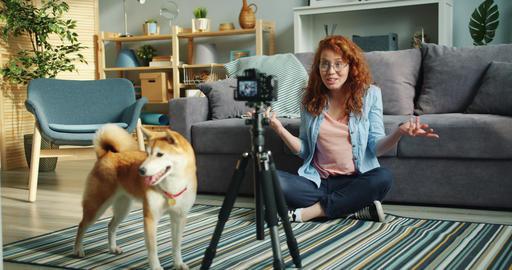 Slow motion of joyful blogger dog owner recording video using modern camera Footage