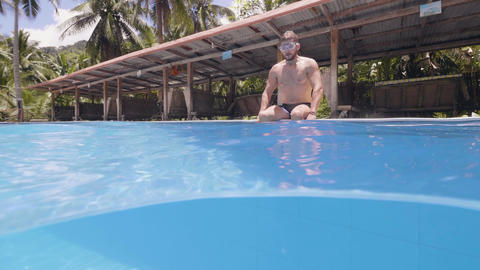 Young bearded man is diving in swimming pool in his vacation on tropical island Footage