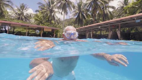 Retied man is swimming in pool outdoor in hotel on tropical island on his Footage