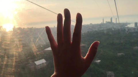 hand touching glass inside funicular cabin, on sunset, tactile sensations Live Action