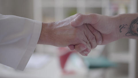Confident friendly handshake of two unrecognized male hands, one in white coats Live Action