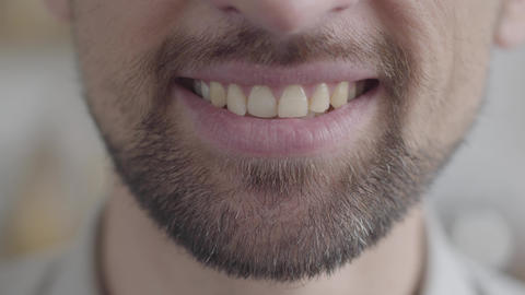 Close-up of the lower jaw of an adult sad bearded man trying to smile with a Live Action