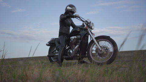 Cute caucasian woman in a black leather jacket and helmet riding a classic Live Action