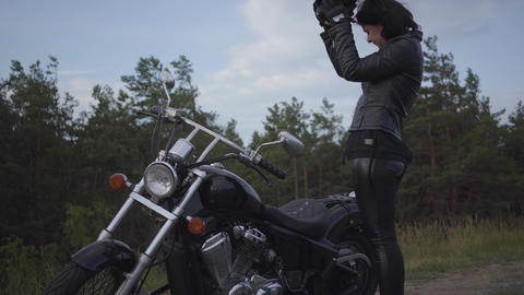 Skill caucasian woman in a black leather jacket and helmet riding a classic Live Action