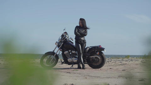 Attractive brunette caucasian girl in leather clothes standing near the Footage