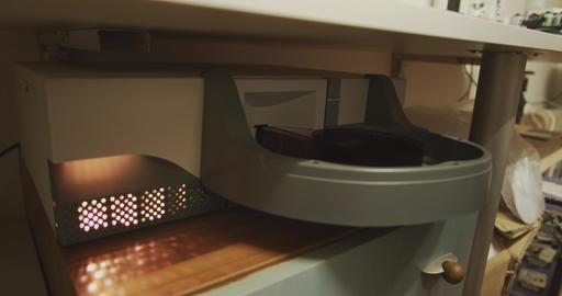 Professional film scanner pulling developed 35mm film negative Footage