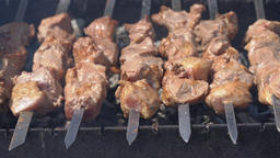 Pork barbecue cooking on metal skewers on outdoors charcoal grill Footage