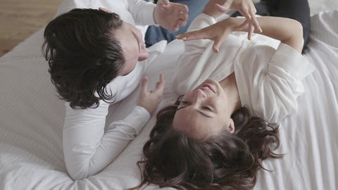 Overhead shot happy young couple lying on the bed talking close-up. Top view Footage