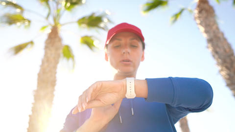 Woman stops while jogging to check the data in the smart... Stock Video Footage