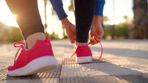 Close up of woman tying shoe laces and running along the palm avenue at sunset Footage