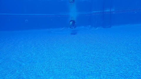 Underwater shooting as a man dives into the pool and swims under the water. Slow Footage