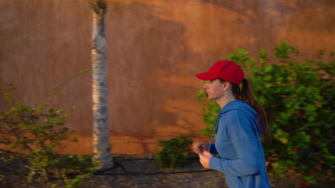 Woman runs down the street among the tropical alley. Healthy active lifestyle Footage
