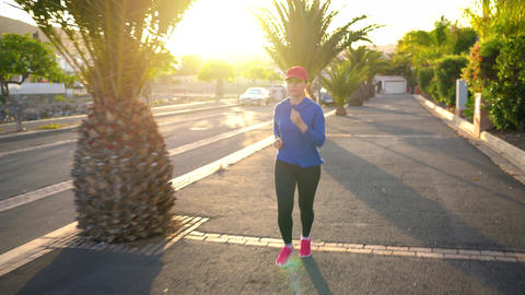 Woman runs down the street among the palm trees at sunset. Healthy active Footage