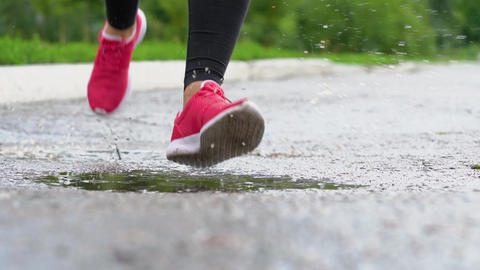 Legs of a runner in sneakers. Sports woman jogging outdoors, stepping into muddy Footage