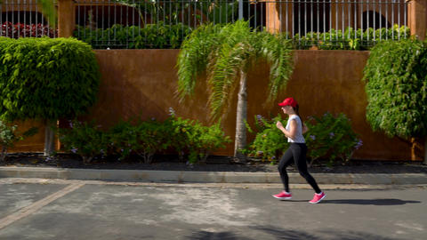Woman runs down the street among the palm trees. Healthy active lifestyle Footage