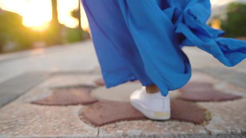 Legs of a woman in a beautiful blue dress walking along the palm avenue. Back Footage