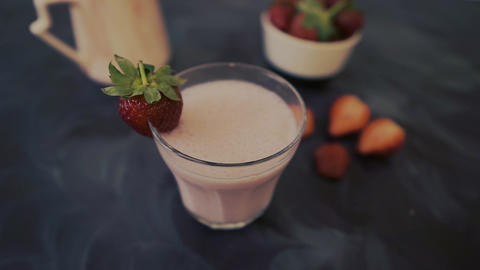 Strawberry milkshake in a glass. A woman pouring coconut Live Action