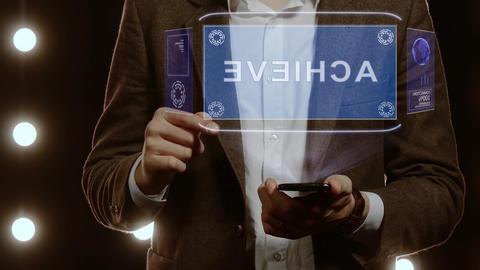 Businessman shows hologram with text Achieve Live Action