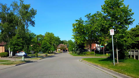 Driving Residential City Road With Lush Trees During Summer Day. Driver Point of View POV Along Footage
