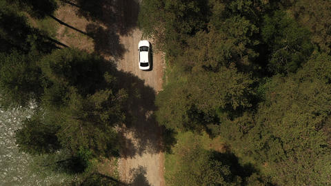 Aerial top drone view. White sedan car moving on dirt road on banks rapid turbulent river. Road Live Action