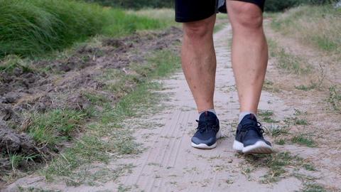 adult athlete in blue sneakers and black shorts walks on the road Acción en vivo
