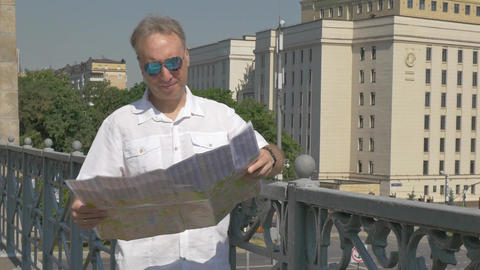 man looks at a paper map of the city and goes to look at the historical place Live Action