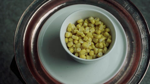 Sweet cnned corn in white bowl. Vegetarian snack Live Action